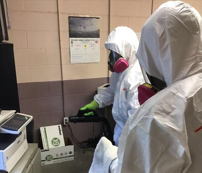 Two SERVPRO employees in PPE in front of equipment