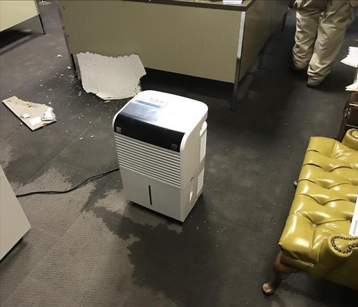 A dehumidifier sitting in the middle of soaked carpet